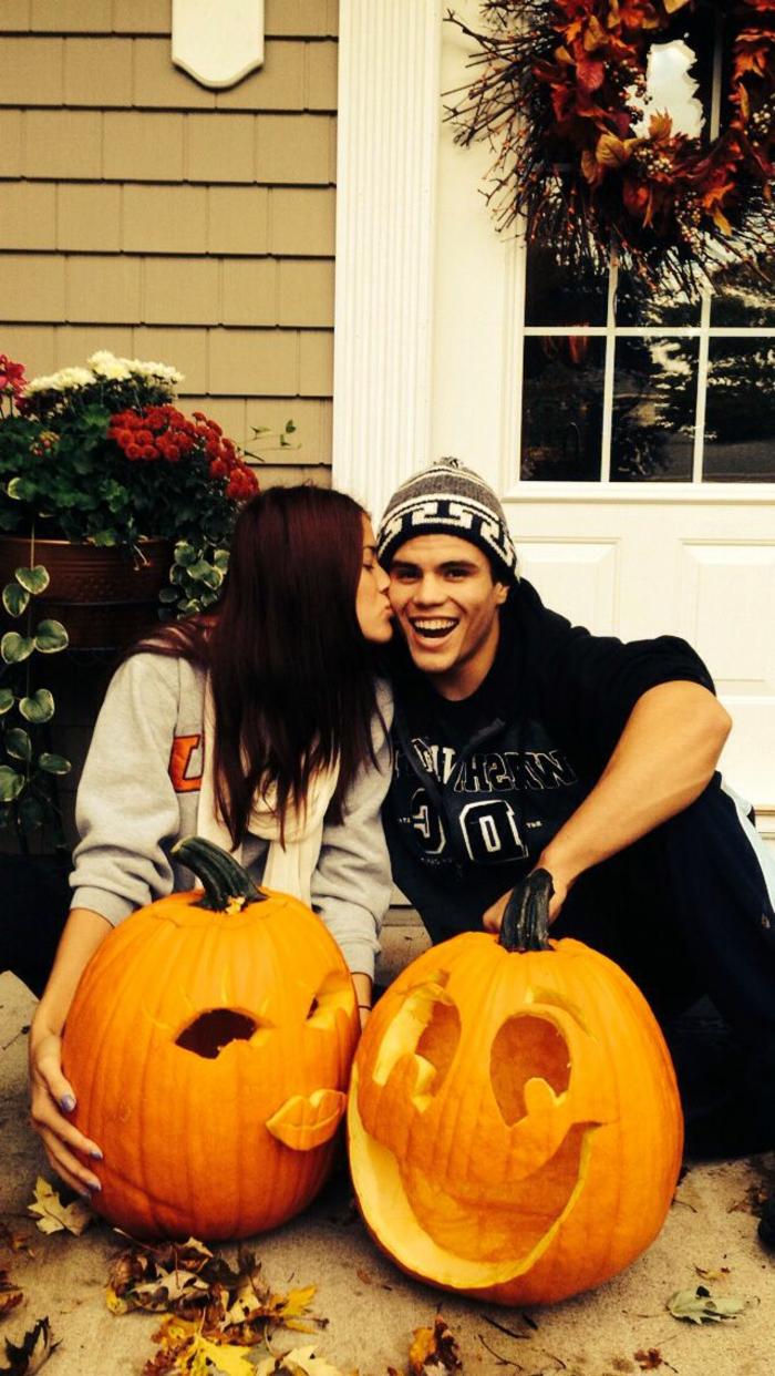 calabazas Halloween, pareja jóven besándose con dos calabazas talladas