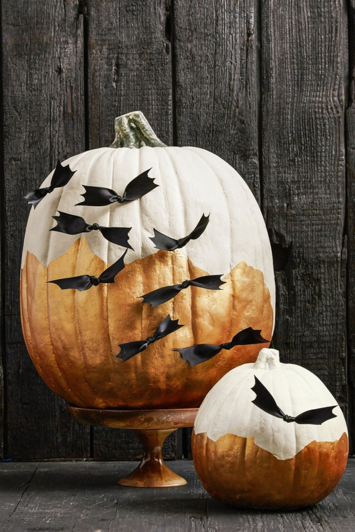 calabazas decoradas, calabazas pintadas en dorado y blanco para Halloween con murciélagod de cinta