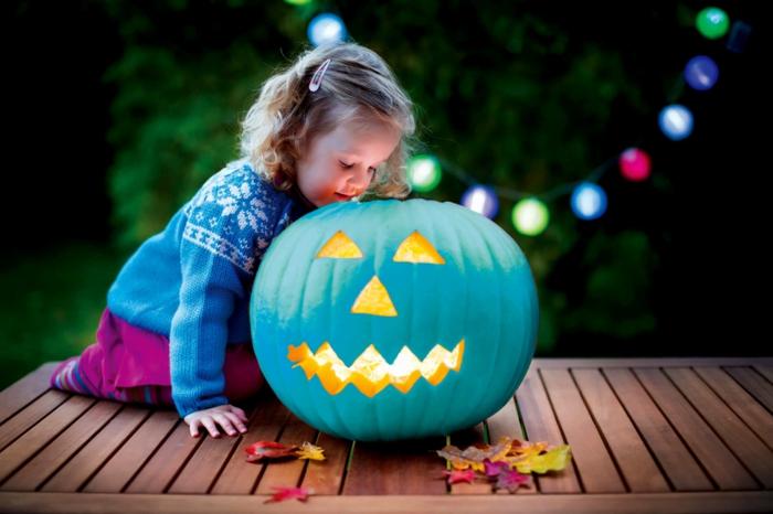 calabazas decoradas, calabaza azul tallada para Halloween, niña pequeña