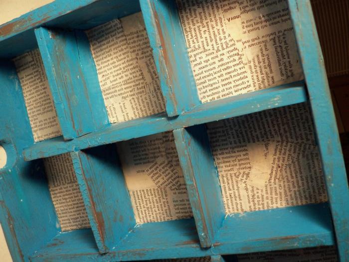muebles con palets, estantería con palets reciclada pintada en azul con fondo cubierto de periodico