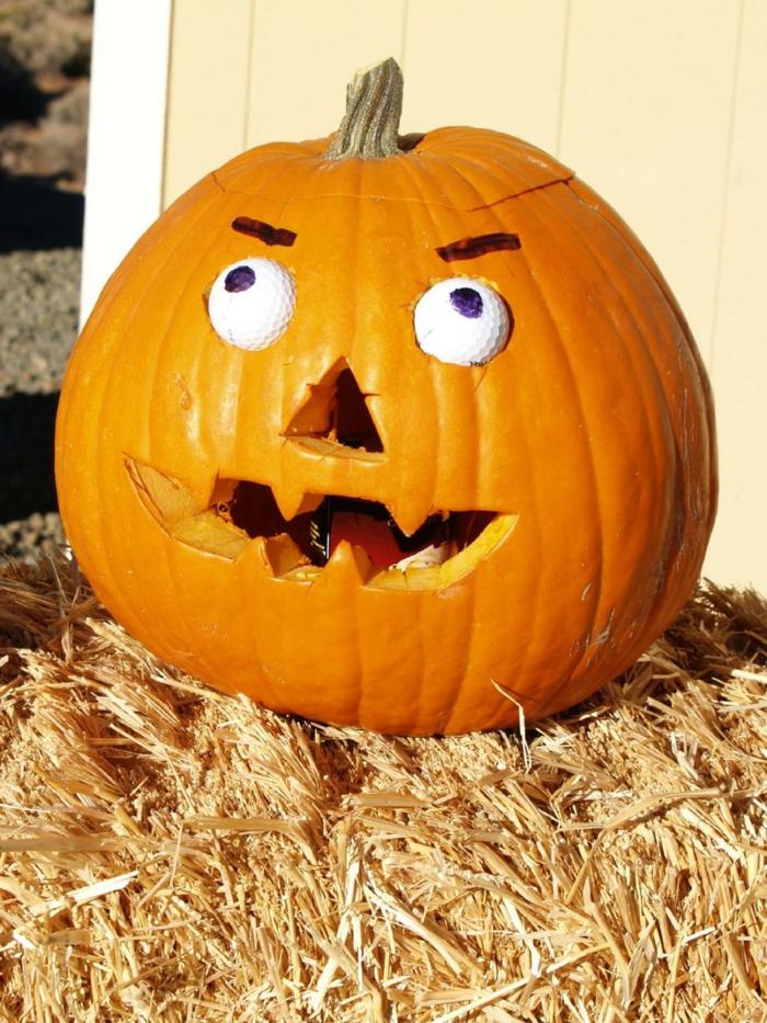 fotos de calabazas de Halloween, calabaza tallada con cara con caras de bolas de golf