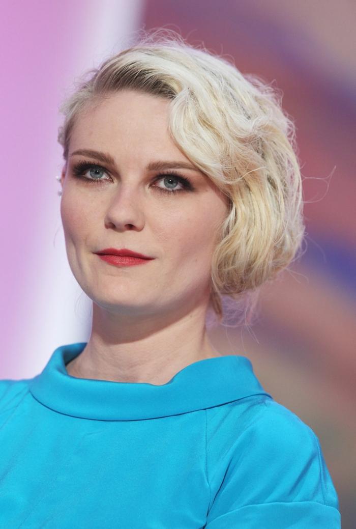 cortes de pelo corto mujer, Kirsten Dunst rubia con vestido azul, corte bob con raya a lado