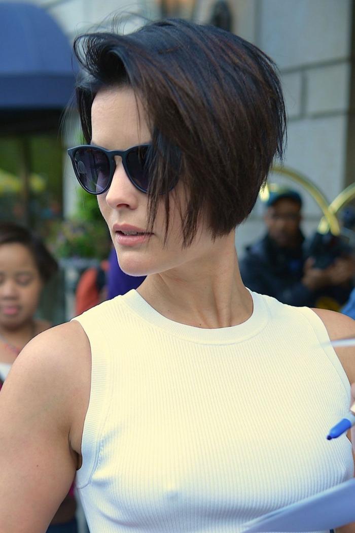 melenas cortas, mujer con pelo corto corte bob, raya a lado, blusa blanca, gafas de sol