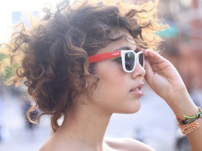 peinados pelo rizado, mujer de perfil con pelo rizado estilo bob, gafas de sol en rojo y blanco