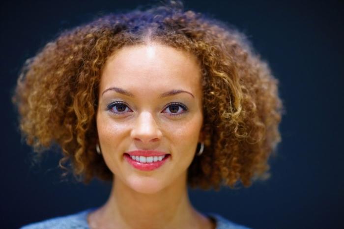 peinados pelo rizado, mujer con cabello afro, corte bob con raya en medio y pendientes