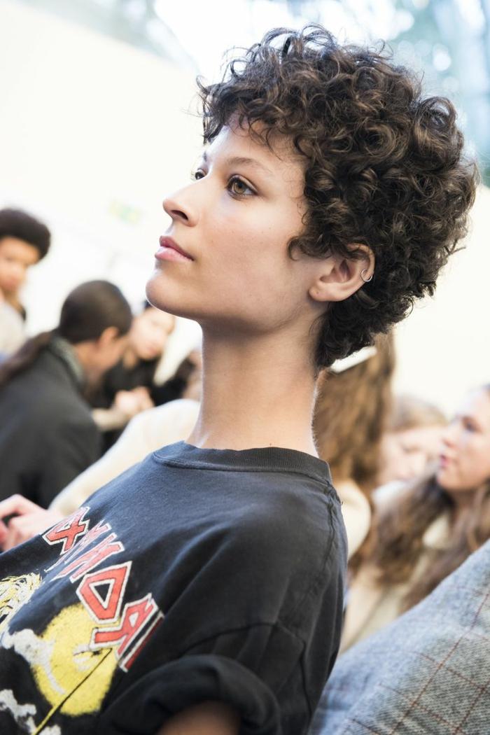 media melena rizada, mujer de perfil con camiseta metallica, corte pixie rizado