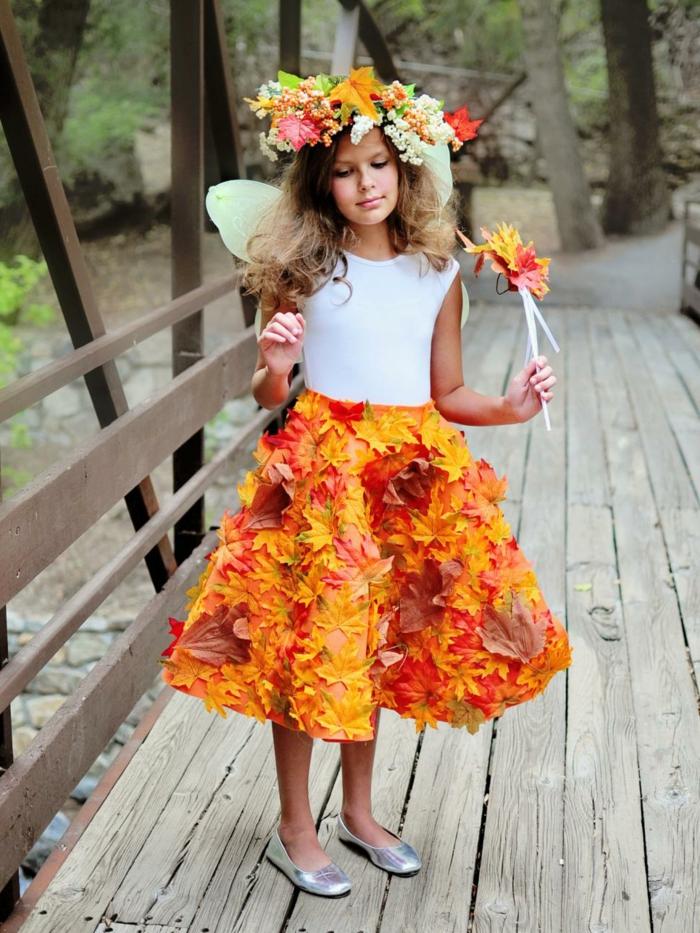 disfraz casero, niña disfrazada de hada con falda de hojas otoñales y alas
