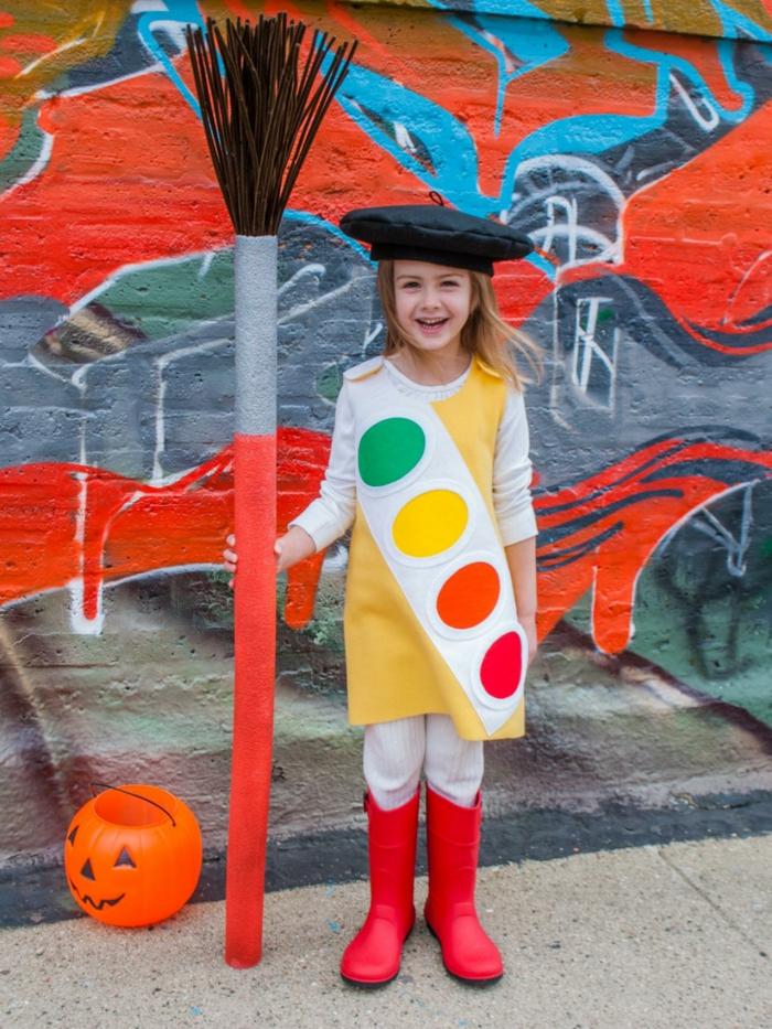 disfraces originales caseros, niña disfrazada de paleta de pintura con pincel grande y pared