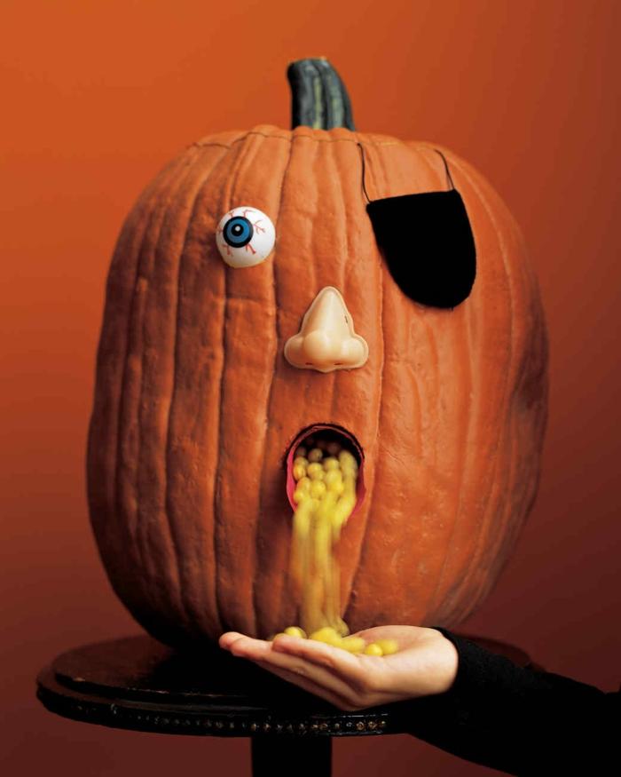 como hacer una calabaza de Halloween, calabaza tallada con ojo de pirata y boca con bombones