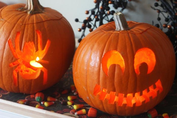como hacer una calabaza de Halloween, calabazas color naranja talladas en forma de araña y cara