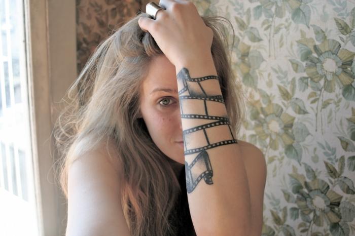 tatuajes en el brazo, mujer rubia con tatuaje en el antebrazo con cinta de cámara