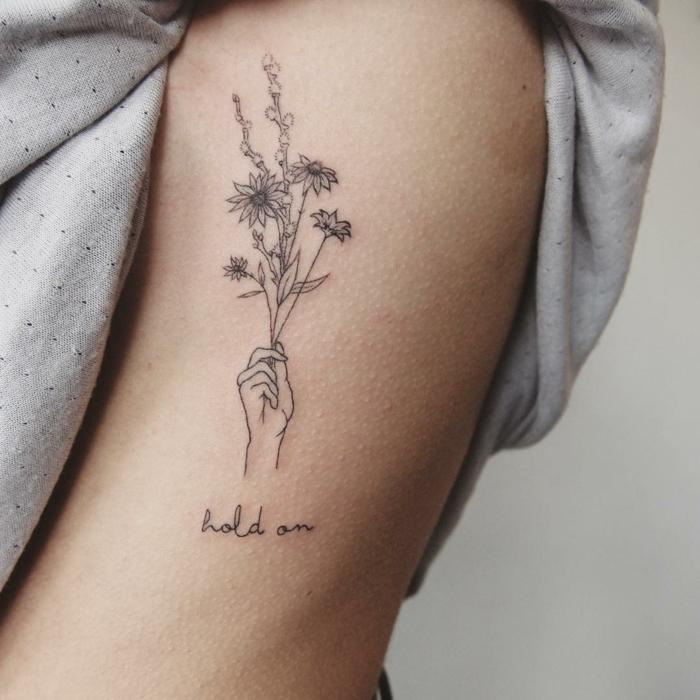 tatuajes antebrazo, tatuaje mujer con mano y flores, frase hold on