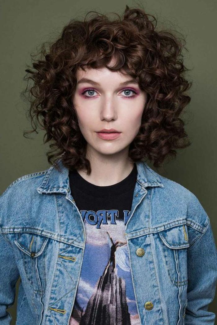 cortes pelo rizado, mujer con chaqueta jeans, corte bob con flequillo regular