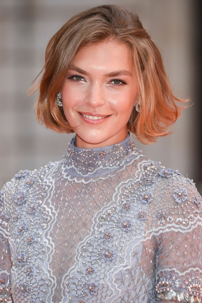 cortes de pelo mujer, mujer sonriente en vestido gris, pelo corto rubio efecto despeinado