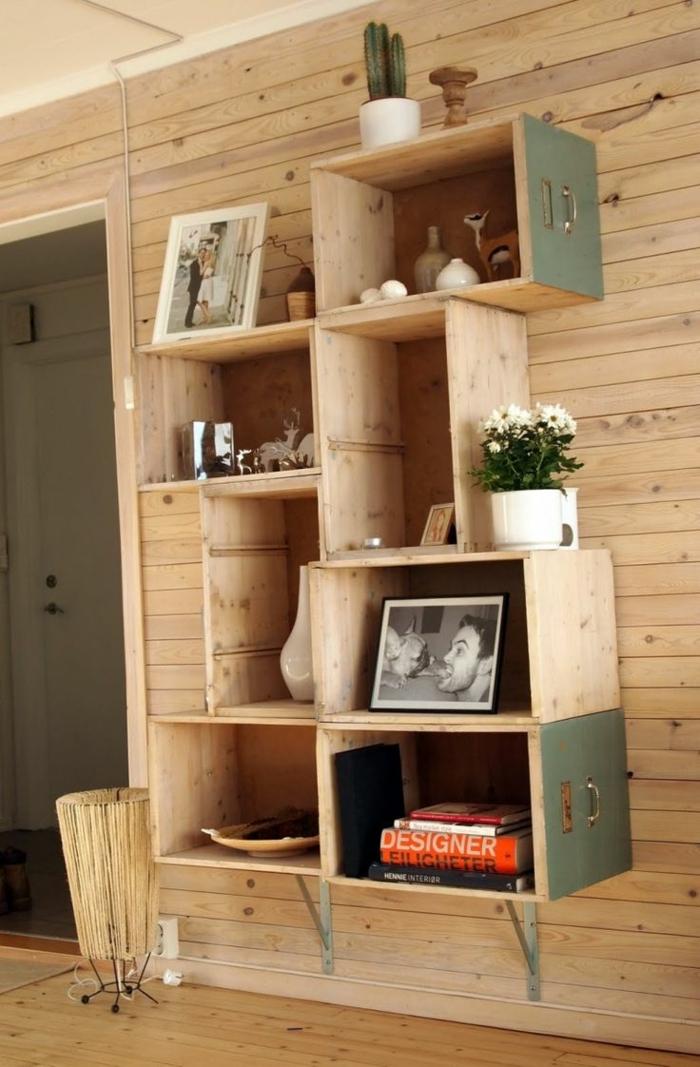 muebles con cajas de fruta, estantería asimetrica de palets y cajones reciclados, libros, plantas, fotos, pared de madera