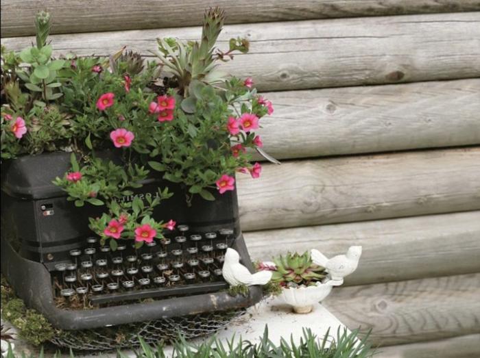 muebles reciclados, máquina de escribir negra convertida en meceta de flores de jardín
