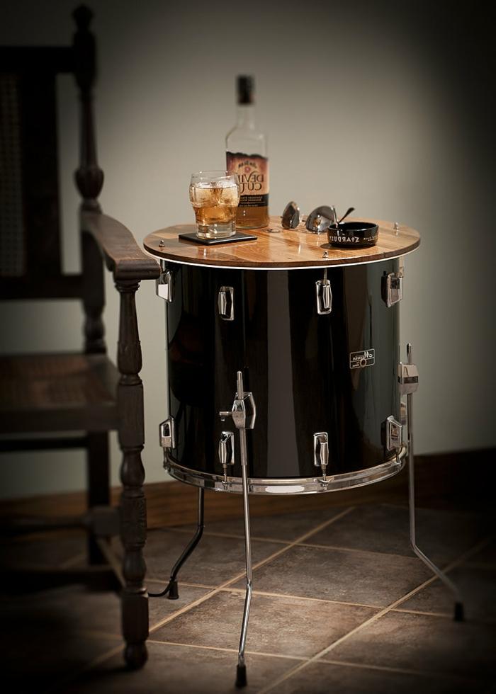 muebles reciclados, mesa auxiliar hecha de tambor reciclado, barniz negro, gafas de sol, vaso y botella