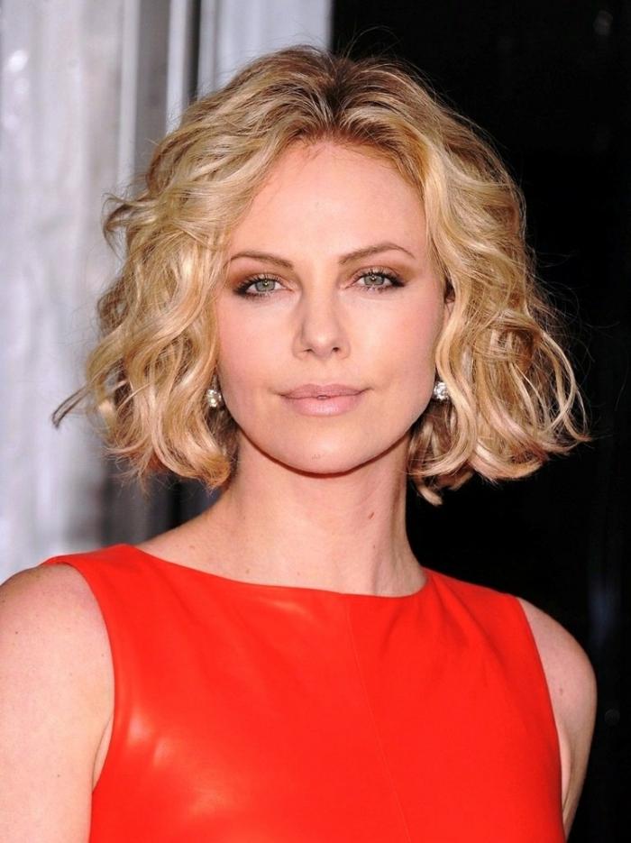 cortes de pelo rizado, Charlize Theron con vestido rojo, corte bob con raya en medio, pelo rubio