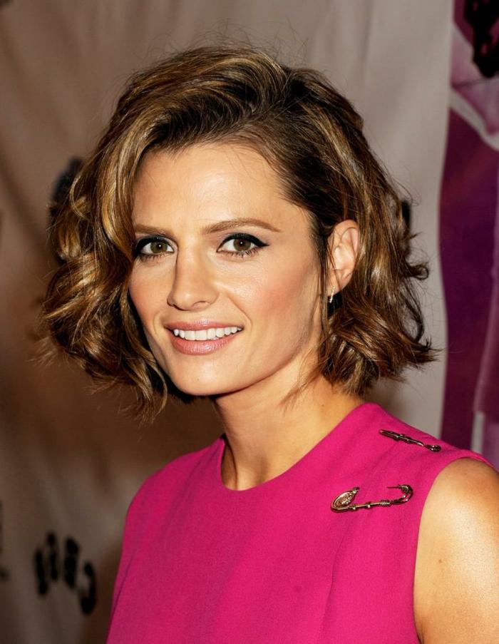 cortes de pelo rizado, mujer con blusa rosa, pelo ondulado con raya ladeada, corte bob