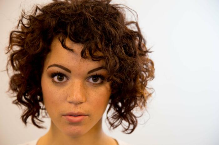 pelo rizado corto, mujer con lunares y piercing, corte bob con flequillo ladeado
