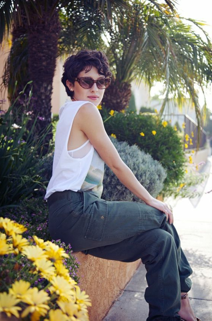 pelo corto rizado, mujer sentada con gafas de sol, corte a lo garçon con flequillo