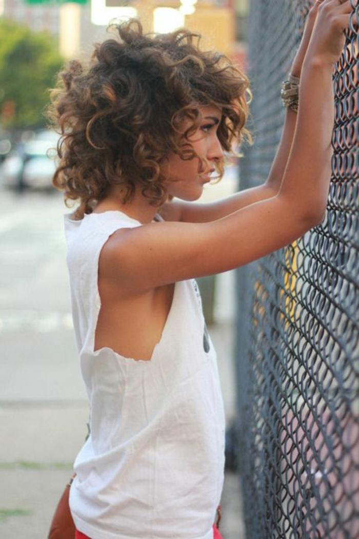 corte de pelo a capas, mujer de perfil con blusa blanca, pelo rizado estilo ombre, corte bob