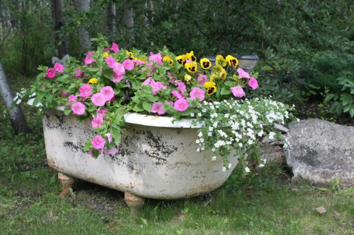restaurar muebles, bañera de cerámica convertida en maceta de jardín con plantas con flor