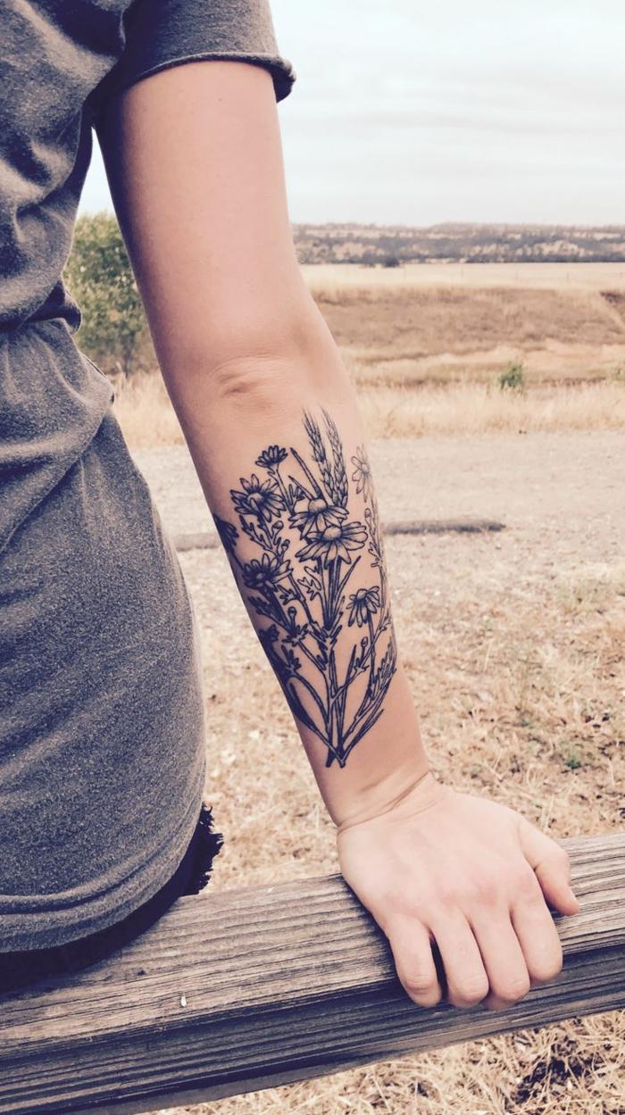 imagenes de tatuajes, mujer sentada con antebrazo tatuado con flores