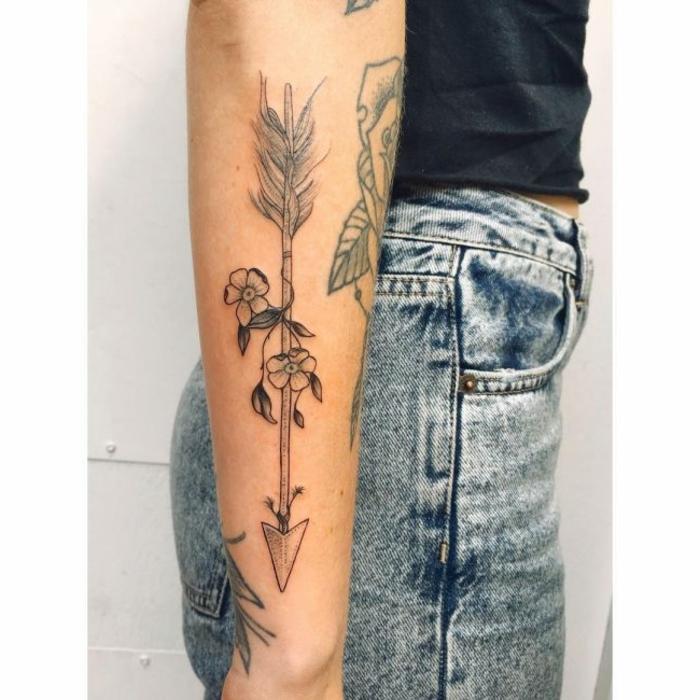 tatuajes originales, mujer tatuada con flecha y flores, blusa negra y jeans
