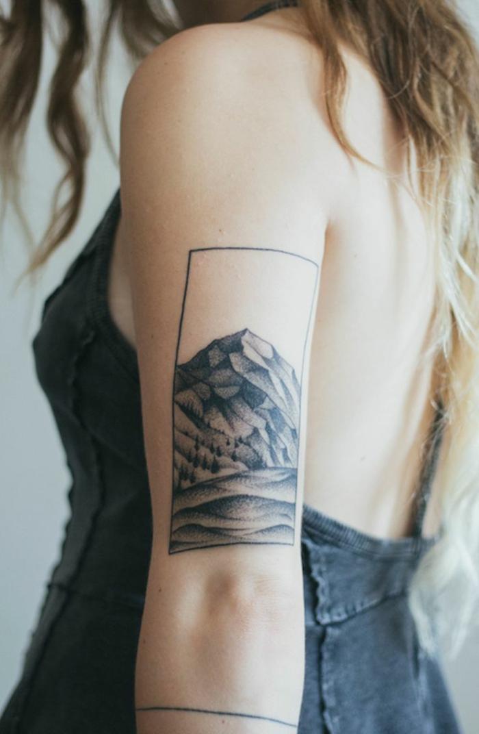 fotos de tatuajes, mujer rubia con tatuaje enmarcado de montaña