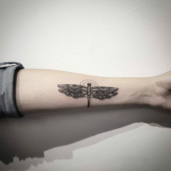 tatuajes con significado. tatuaje con círculo y libélula en antebrazo