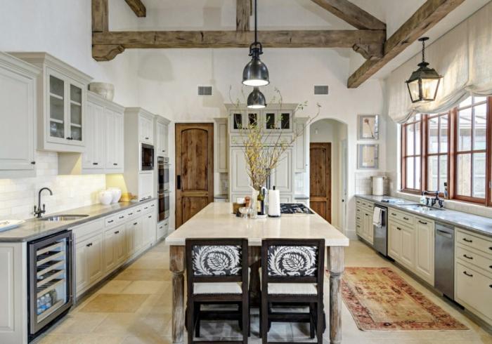 decoracion rustica, cocina larga con mesa de mármol y sillas tapizadas, techo con vigas y alacenas blancas, grandes ventanas