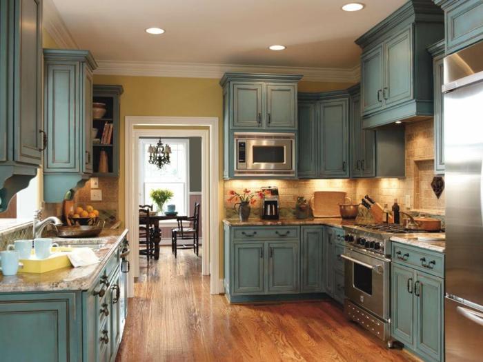 decoracion rustica, cocina con armarios de madera pintada azul pastel, suelo de tarima, puerta al comedor