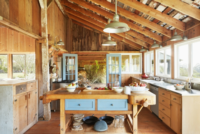 dercoracion rustica, cocina rustica con vigas de techo inclinado, madera clara y azul, isla con cajones