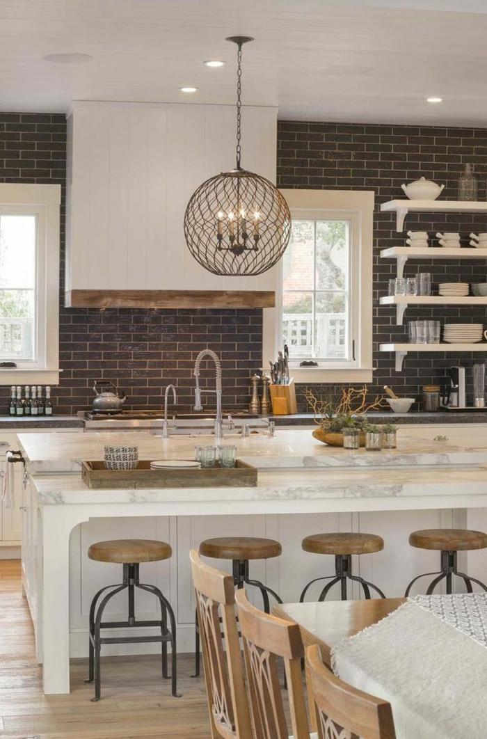 cocinas de obra, cocina rustica con pared de ladrillo, isla de mármol con sillas redondas, lámpara colgante