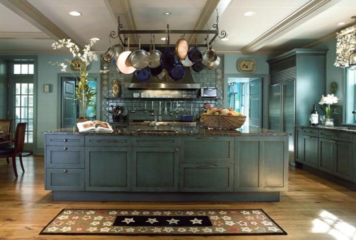 cocinas de obra, cocina en azul con isla grande, suelo de tarima con tapete, sartenes colgantes