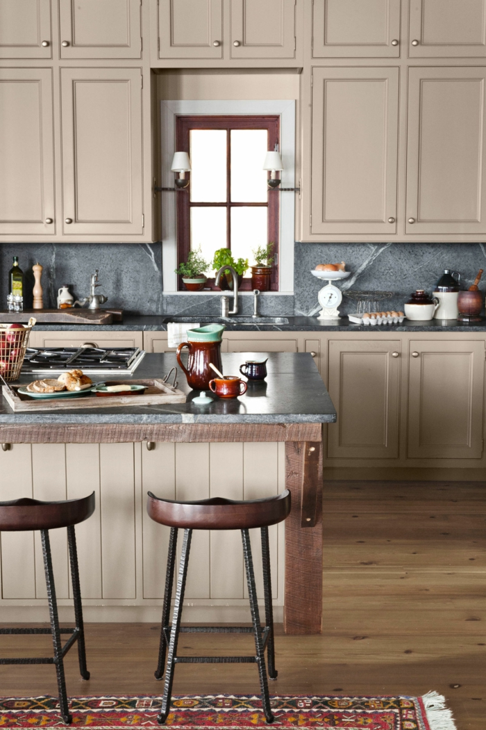 cocinas rusticas, cocinas con alacenas beige, isla con sillas de madera, suelo de tarima con tapete