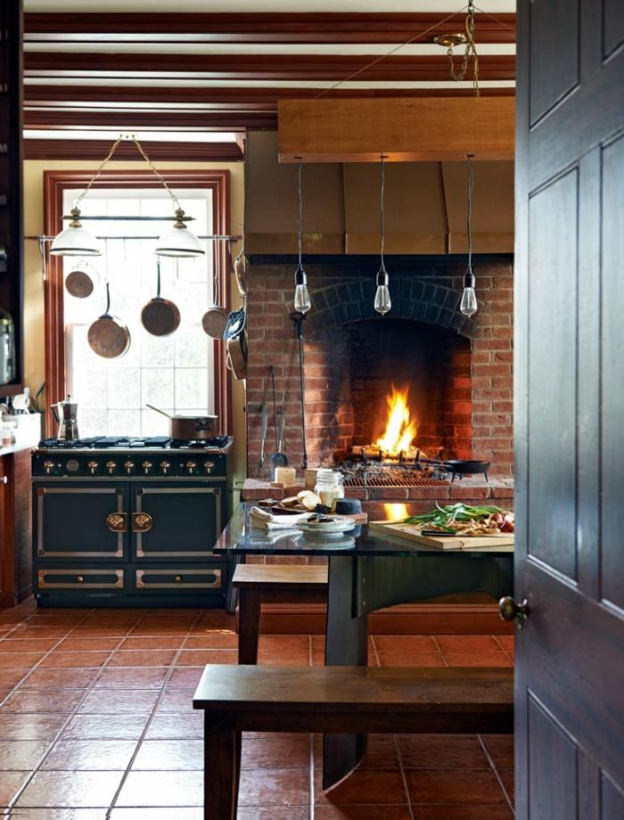 cocinas rusticas, cocina con chimenea de ladrillo encendido, sartnes colgantes, mesa y suelo de baldosas