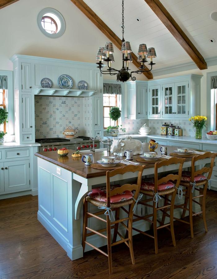 cocinas rusticas, cocina en madera azul con isla y sillas altas con cojines, lámpara de araña y ventana redonda