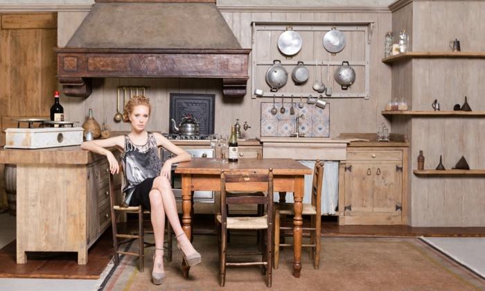 cocinas modernas pequeñas, cocina madera rústica, mujer sentada, mesa sillas desparejas, decoración con sartenes y ollas