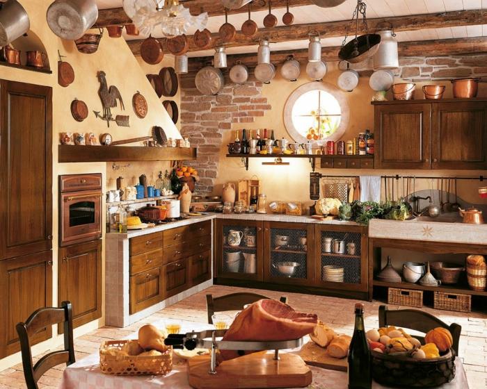 cocinas modernas pequeñas, cocina rustica con pared de piedra, decoración con sartenes colgantes, centana redonda