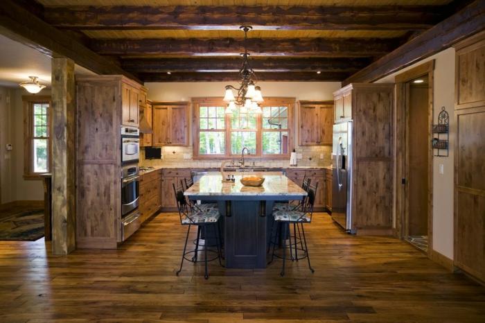 cocinas rusticas de obra, cocina grande oscura con lámpara de araña. muebles de madera rústica, mesa de mármol