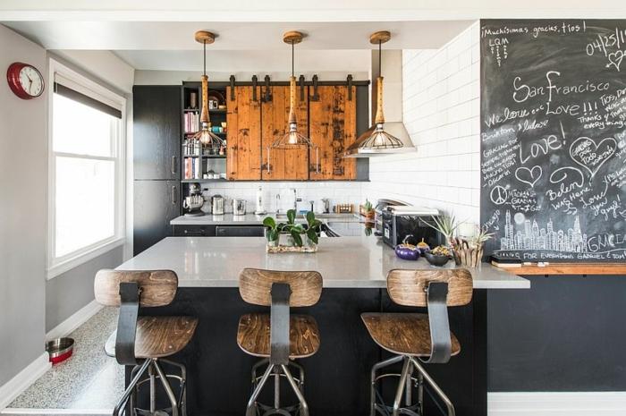 cocinas con encanto, cocina rústica con isla y sillas altas, pared pizarra, lámparas colgantes