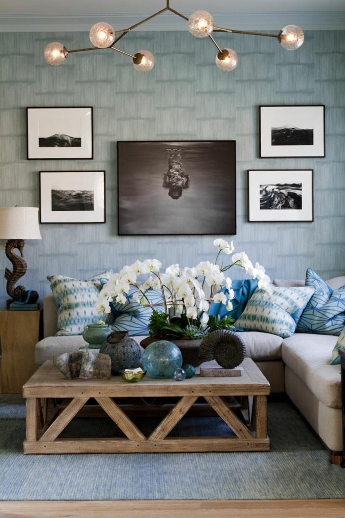 salones modernos, salon en azul, mesa de madera con flores blancos, cuadros, cojines y bombillas
