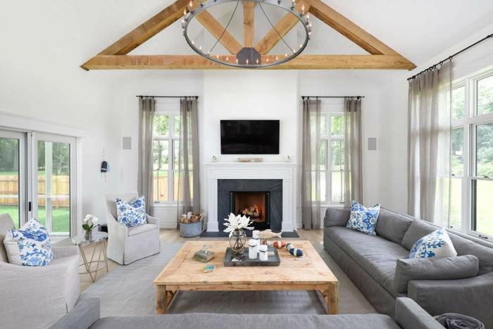 salones modernos, estilo rustico con lámpara de araña, sofá gris, chimenea, televisor y cojines en azul