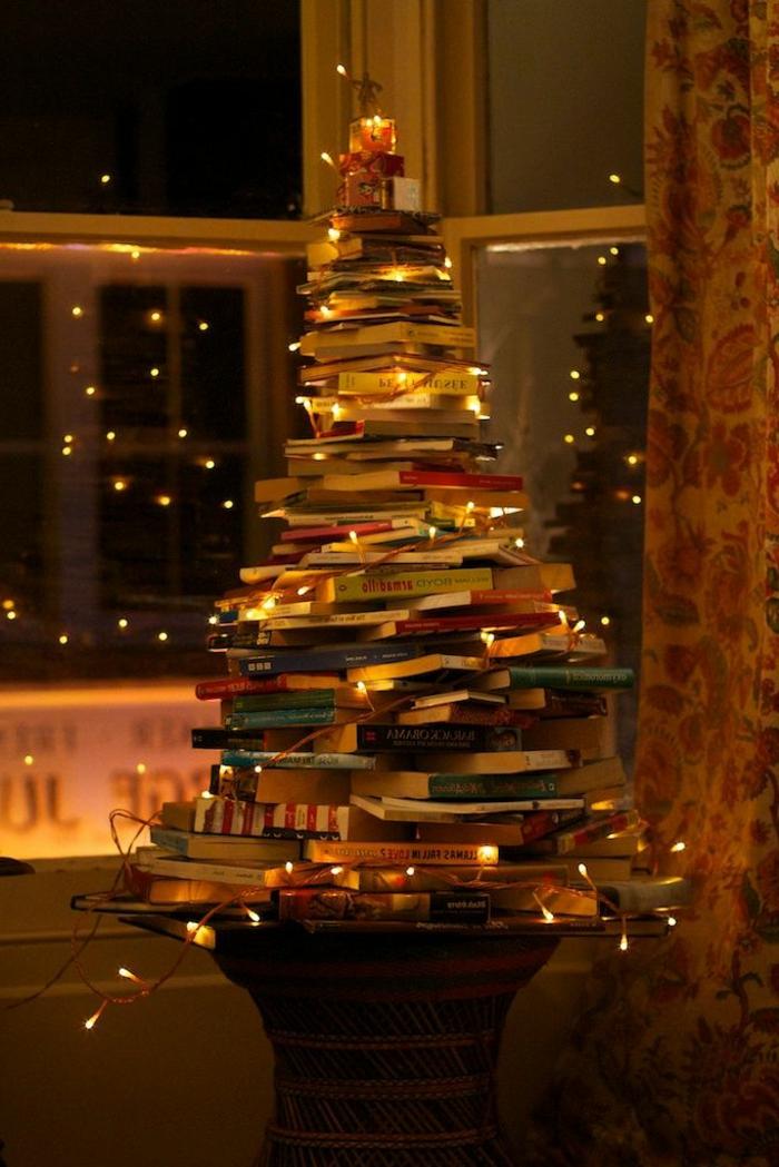 motivos navideños, libors instalados en forma de árbol, lámparas amarillas