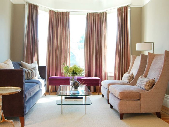 salones con encanto, salón con techo alto, grandes cortinas, sillones rosados, sofá azul, mesa de vidrio con flores