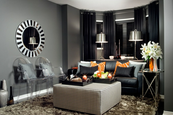 salones con encanto, salón poqueño en gris y negro con sillas de plástico transparente, cortinas y sofá en negro, cojines naranja