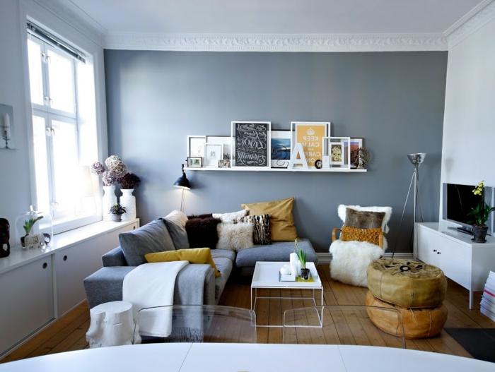 salones con encanto, salón con comedor, sofá azul en forma de L con cojines amarillos, pared azul, estantería con cuadros, taburetes y telivisor