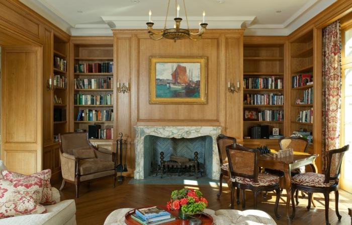 muebles salon, salon rustico con cuadro marino, librería y chimenea, flores y sofá con cojines